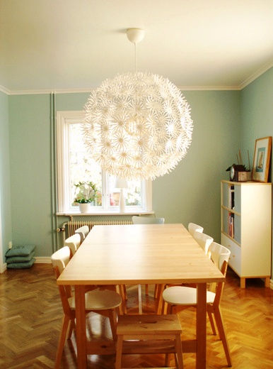 Light blue kitchen with herringbone wood floor and a Dandelion ceiling light from Ikea