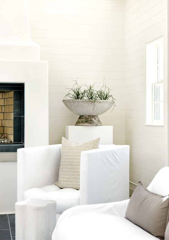 Close up of a white armchair in an all white living room