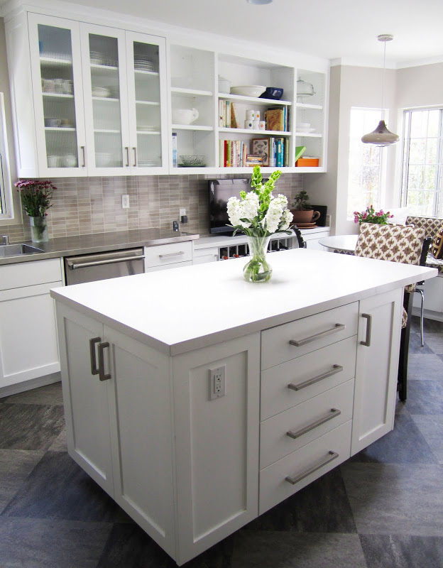Gourmet kitchen with grey/brown backsplash, white paneled cabinets and hood and grey tiles arranged in a diamond pattern