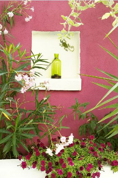 Pink outdoor wall with a white nook holding a bright green bottle