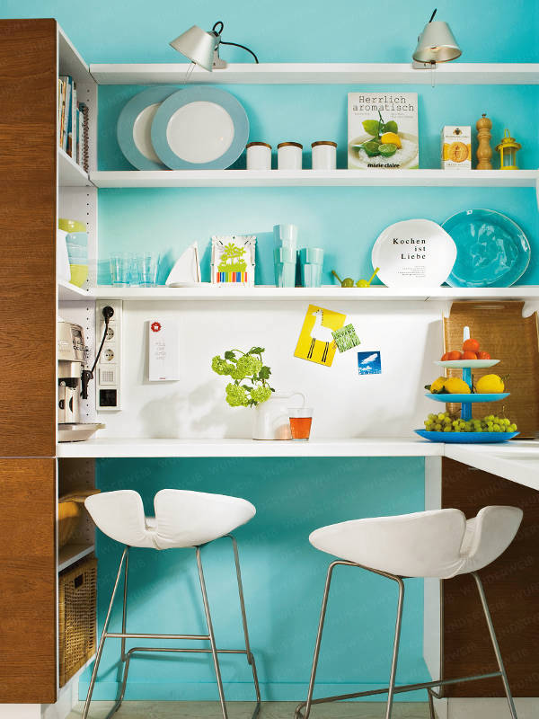 Small turquoise kitchen with floating shelves and a small bar