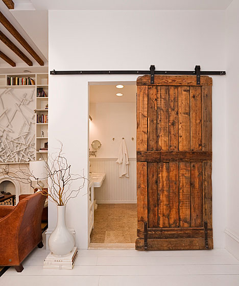 All in one kitchen, dining room, guest bedroom and small bathroom with reclaimed barn door being used as a bathroom door