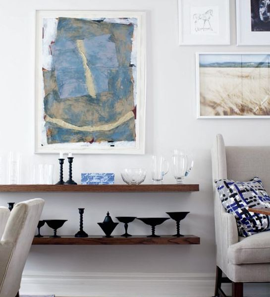 Floating shelves and a wall full of art in a small dining room in a cottage