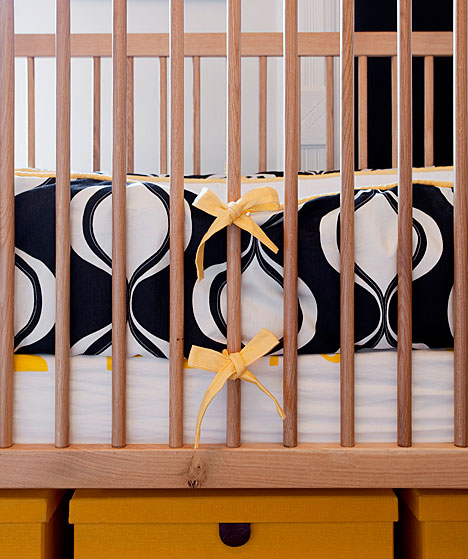 Close up of a crib with yellow and navy bedding