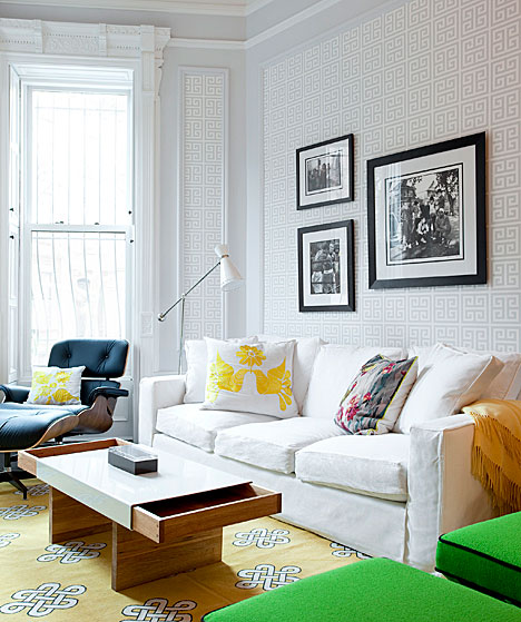 Living room with Greek key wallpaper, decorative moldings and a bright rug in Brookyln