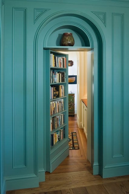 Teal bookshelf doubles as an arched secret library door by Peter Pennoyer