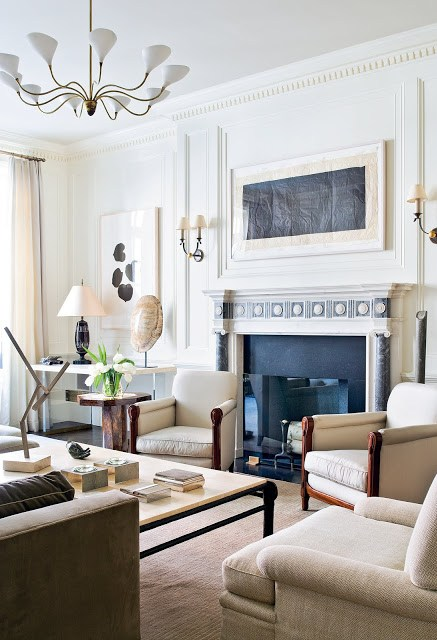 Living room by Peter Pennoyer with decorative moulding, a gold and white chandelier, fireplace with blue and white marble detailing, white armchairs, a taupe sofa, cream are rug, a large coffee table and wood side table