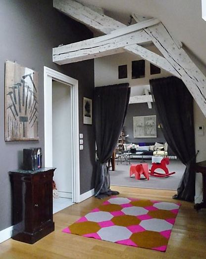 Foyer in a Paris apartment with painted white natural wood beams, grey wall, wood floor and a pink, brown and grey hexagon rug. Instead of a door to the living room, they have curtains