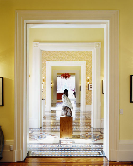 Yellow enfilade with a tile floor and a sculpture of a white owl in the center
