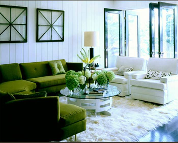 Living room with a green velvet sectional sofa, white beadboard walls, two white armchairs, a round coffee table with a white base and glass top, wood floor and a furry white rug