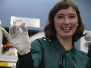 Cassie McFarland holds up Baseball Hall of Fame Commemorative Dollar with her design