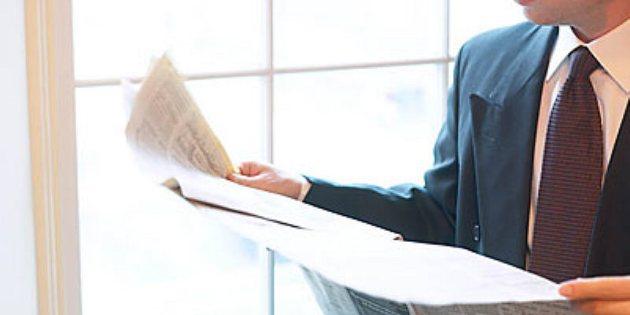 Caucasian businessman reading newspaper beside window uid 1172584