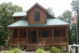 log home with green metal roof