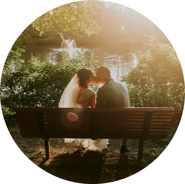 newly wed couple kissing on bench