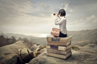 girl with binoculars-sitting on books