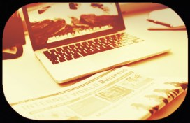 image laptop-beside-newspaper
