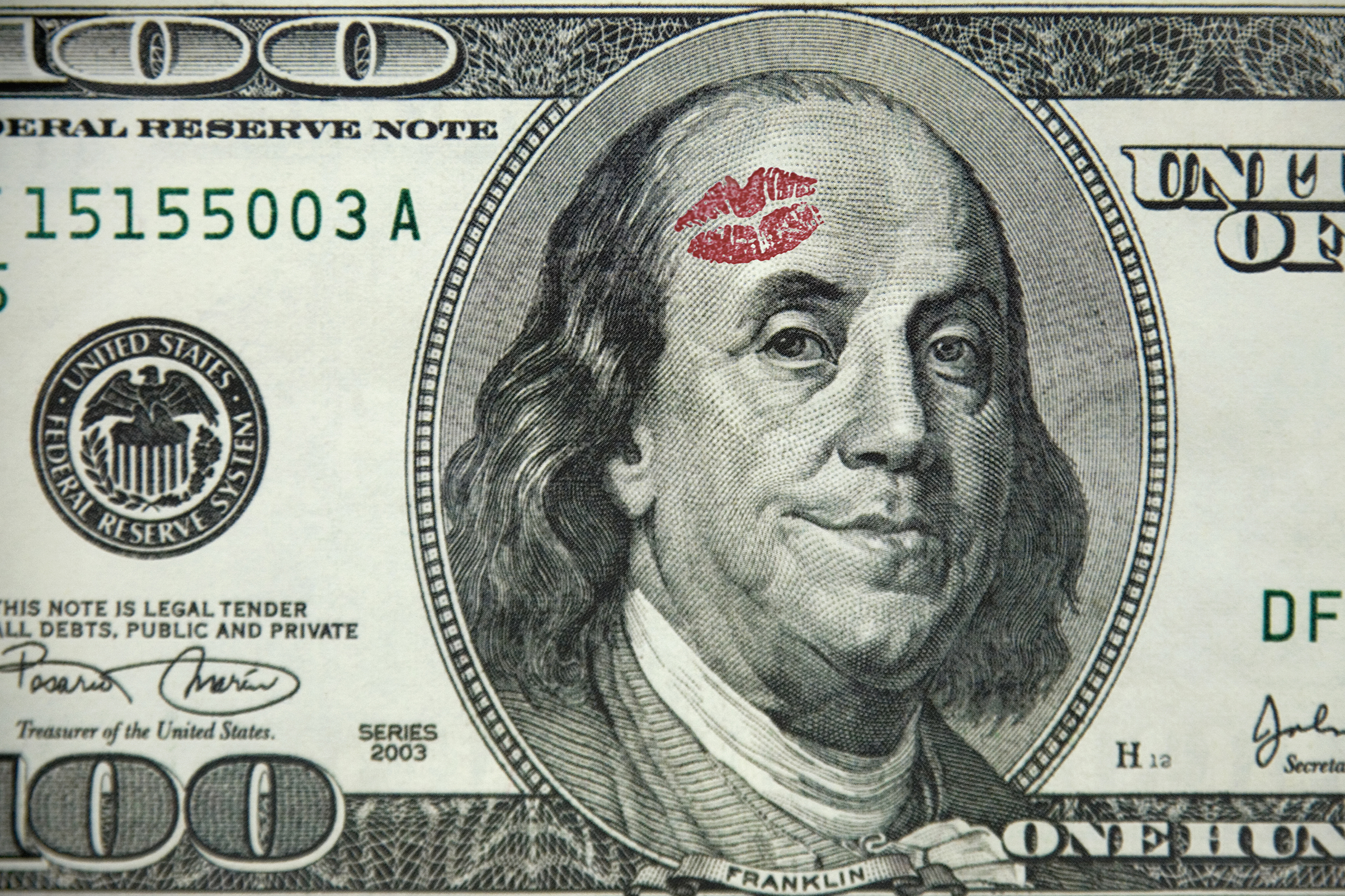 Ben Franklin, on a hundred dollar bill, smiles, having recieved a kiss on the forehead