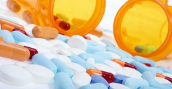 Stock image of pills, capsules and tablets of different colors over white.