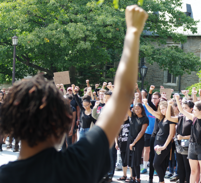 Protestors raise their fists at a Black Students United Rally on Friday.
