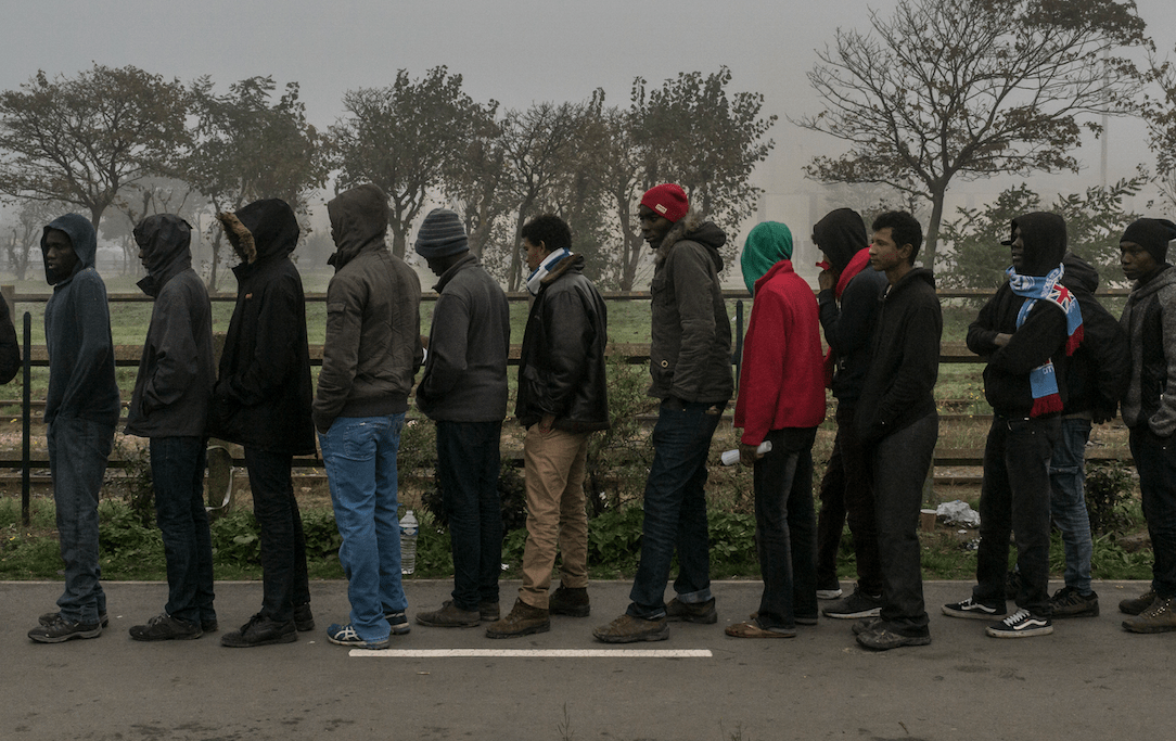 Refugees wait to be registered at a makeshift camp where 6,000 or more have been living in Calais, France.