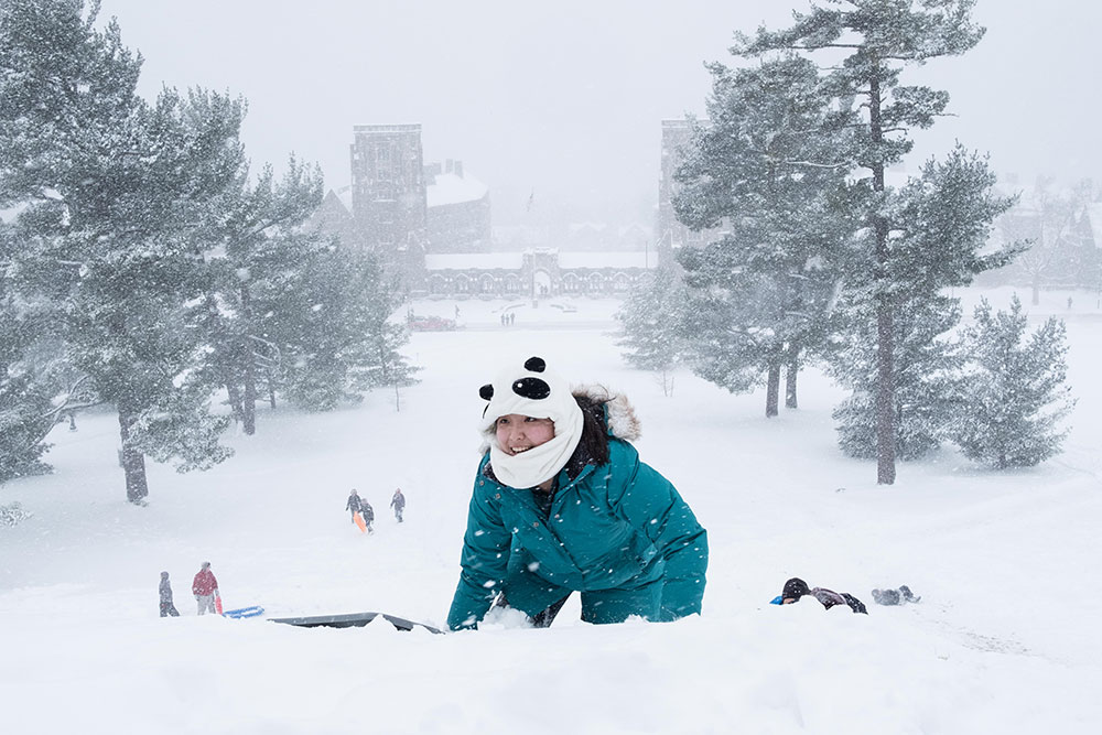 Michelle Xiong '18 looks up from the snow at the top of Libe Slope on Tuesday.
