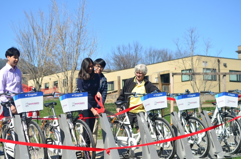 Students participate in ribbon cutting for the launch of Big Red Bikes on Saturday.