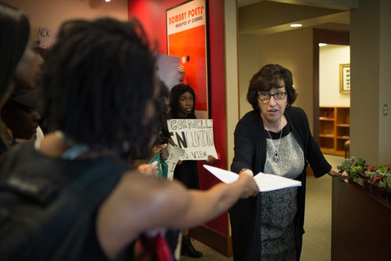 Delmar Fears '19, co-chair of Black Students United, hands a list of demands to Cornell President Martha Pollack in Day Hall on Wednesday, Sept. 20, 2017.