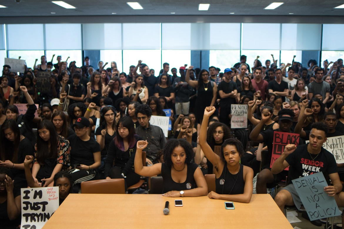 250 people, including Black Students United Co-Chairs Traciann Celestin '19 and Delmar Fears '19, center, packed into Clark Hall on Tuesday to support BSU after an assault in Collegetown in which a black student said he was punched repeatedly by several white men and called the N-word.