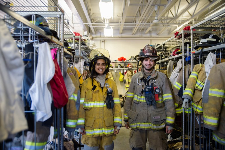 Meeta Shrivastava '19 and Blake Berger '15, two of many Cornellians volunteering at the Cayuga Heights Volunteer Department, pose in front of racks of gear on Monday.