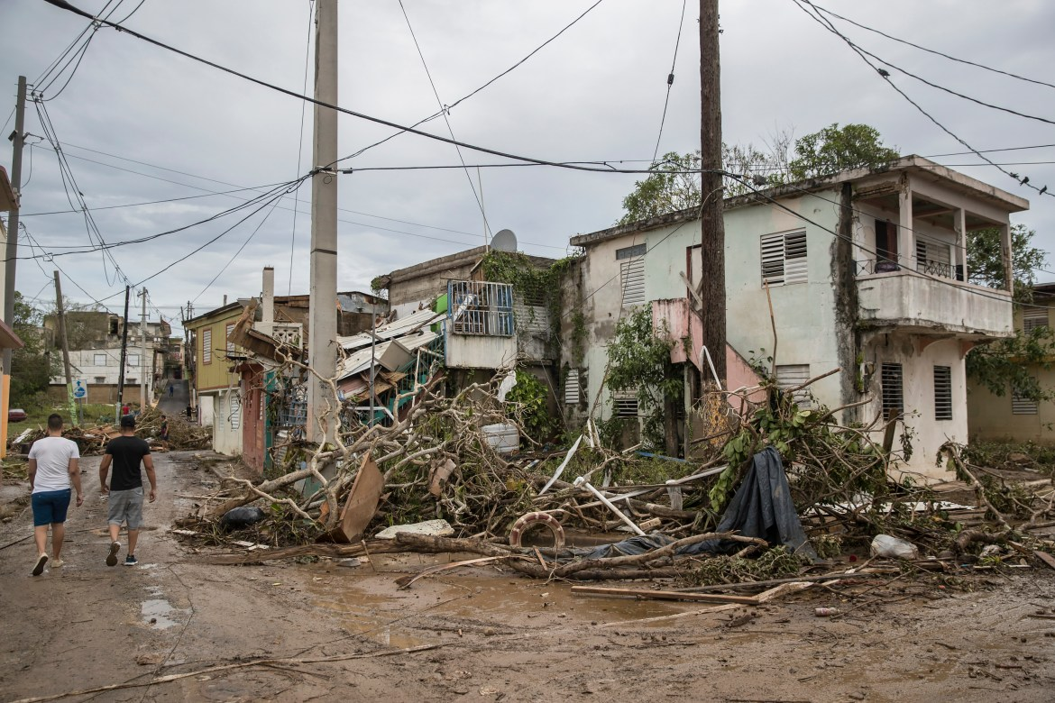 People pass debris from Hurricane Maria in Arecibo, Puerto Rico.