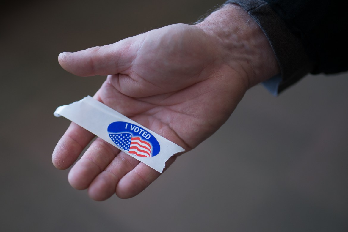 "Rev. Steve Felker, of Ithaca, holds out an ""I Voted"" sticker at the polling place at Alice Cook House Tuesday morning."