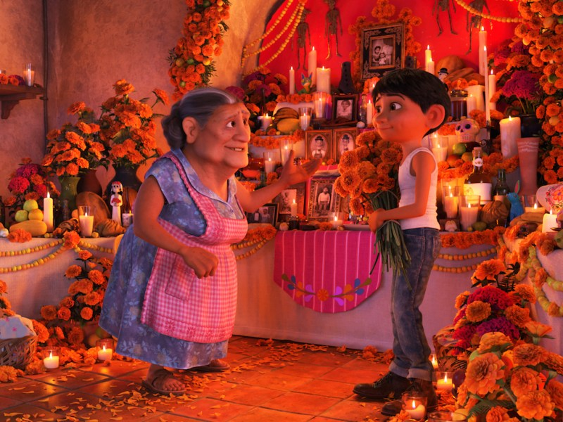 Miguel talks to his grandmother in front of the ofrenda in the recent Pixar release Coco.