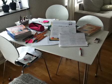 Papper, pennor, pärmar och böcker i en salig röra.