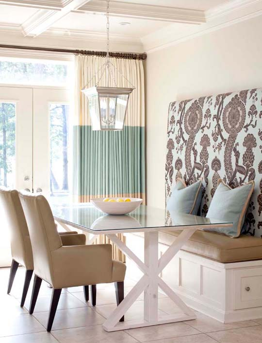 Breakfast nook with leather armchairs and an upholstered bench with turquoise and white striped curtains