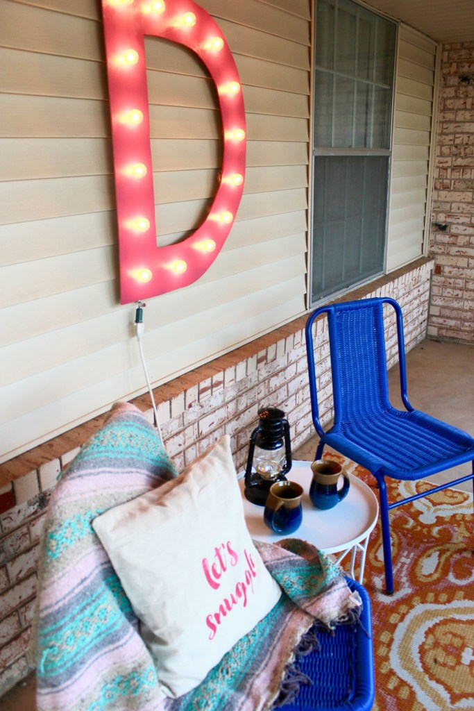 blue chairs front porch giant marquee light lantern pillow blanket
