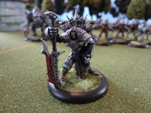 Warmachine miniature figure Goreshade kneels in foreground while death waits behind him.