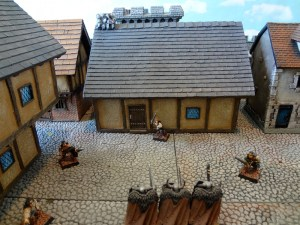 Approaching Chaos Warriors threaten the prepainted Pegasus Hobbies Tudor-style house