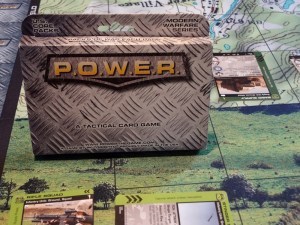 Steel box for POWER sits on playing matt with P.O.W.E.R. cards deployed to play