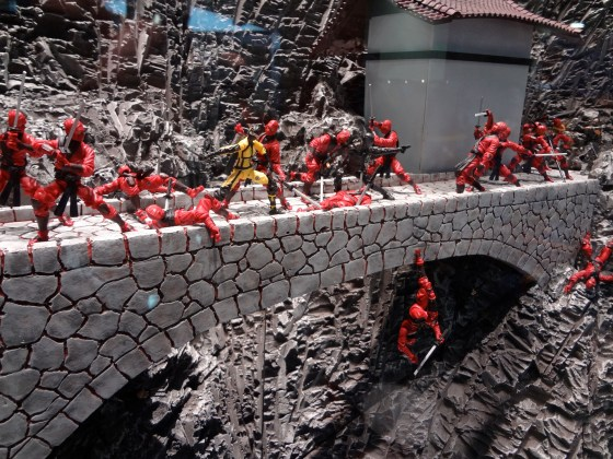 Red Ninjas lay dead or falling in a bridge attack action figure vignette from Hasbro with a grey mountain backdrop