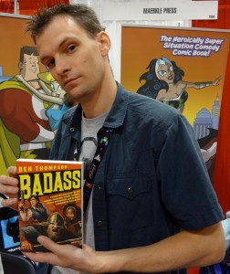 Author Ben Thompson at Comic-Con holding up his book Badass