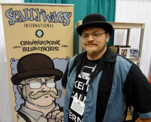 Mustachioed Darren Gendron at his booth with a comic version of himself drawn by Obsidian Oracle