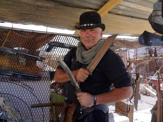 Weapon Maker David Baker as Mr. Dark with post-apocalyptic kukris at Wasteland Weekend in black bowler
