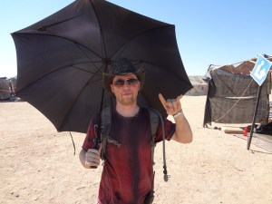 Black umbrella protects Wasteland Weekend cofounder Jared from desert heat near California City