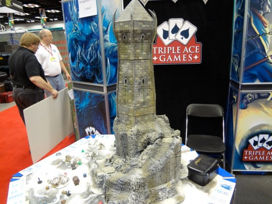 Iceblade Keep rises out of a snowy terrain board. Colossal tower with miniatures on the table