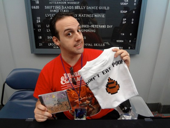 3d6 Bassist Anthony Bassett in a red box D&D shirt holding tshirt that reads don't eat poop and CD of album Damage