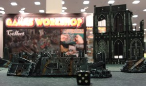 Painted miniature terrain from Cities of Death in foreground before Games Workshop banner display