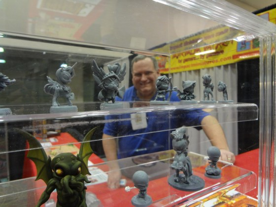 Miniature display case in foreground with tentacled Cthulu and pony while Tom Anders is in background smiling