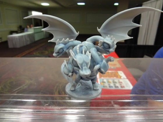 Five-headed plastic chibi Hydra with wings on display stand at GAMA Trade Show