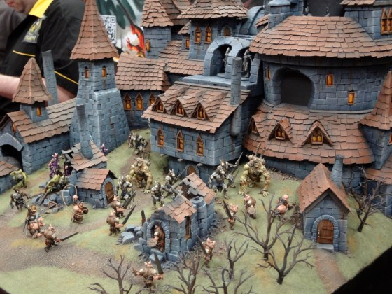 Beautiful stunning diorama of 32mm Wrath of Kings miniatures clashing at a castle or village