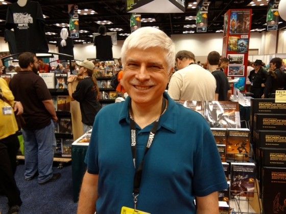 White-haired RPG Designer and Legend Kevin Siembieda smiling in crowded Gen Con Exhibitors' Hall